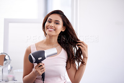 Buy stock photo Portrait of an attractive young woman drying her hair with a hairdryer in the bathroom at home
