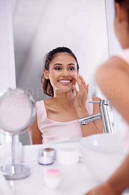 Buy stock photo Portrait of an attractive young woman applying moisturiser in front of a bathroom mirror