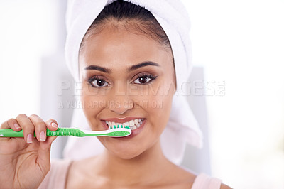 Buy stock photo Portrait of a young woman brushing her teeth in the bathroom