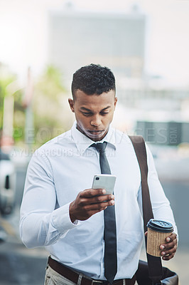 Buy stock photo Shot of a handsome young businessman using a cellphone in the city