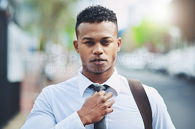 Buy stock photo Portrait of a handsome young businessman adjusting his tie while out in the city