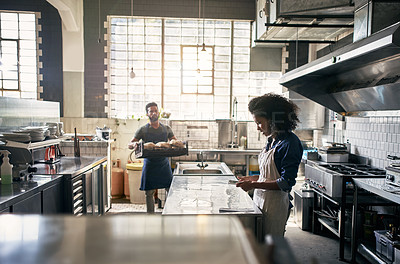 Buy stock photo Cropped shot of two young coffee shop employees working in the kitchen of their cafe