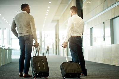Buy stock photo Rearview shot of two businessmen standing in the airport with their luggage