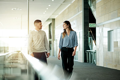 Buy stock photo Cropped shot of two businesspeople walking through a corridor in their workplace