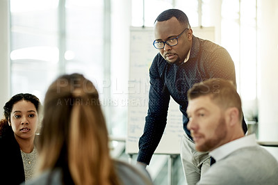 Buy stock photo Cropped shot of a group of businesspeople gathered around a table in the boardroom during a meeting