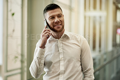 Buy stock photo Shot of a mature businessman talking on a cellphone in a modern office