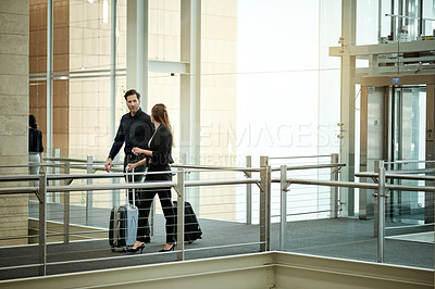 Buy stock photo Shot of two businesspeople walking through a convention center with their suitcases while on a business trip