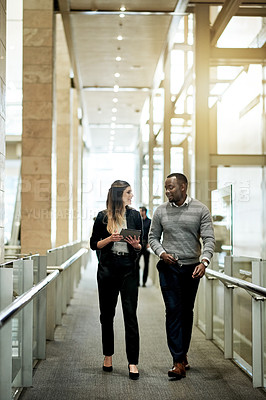 Buy stock photo Shot of two businesspeople having a discussion while walking in a modern office