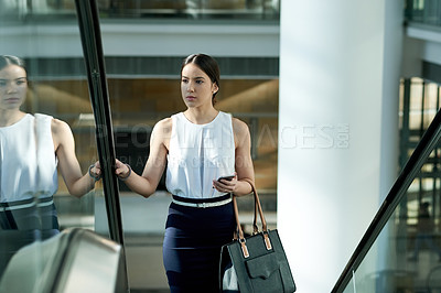 Buy stock photo Cropped shot of a young businesswoman on an escalator