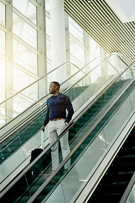 Buy stock photo Shot of a young businessman on an escalator in the workplace