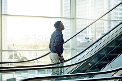 Buy stock photo Cropped shot of a young businessman on an escalator in the workplace