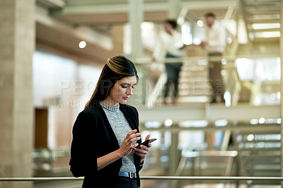 Buy stock photo Shot of a young businesswoman using a cellphone in a modern office