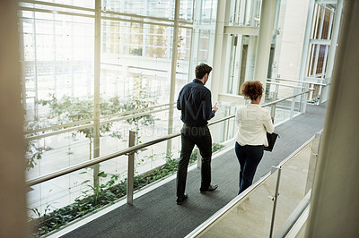 Buy stock photo Rearview shot of two businesspeople walking in a modern office