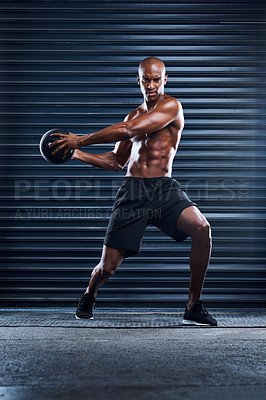 Buy stock photo Shot of a masculine man working out with a medicine ball