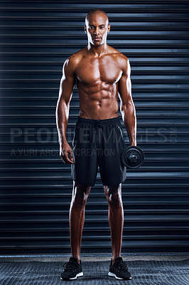 Buy stock photo Shot of a sporty young man working out with weight plates as part of his exercise routine