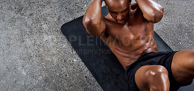 Buy stock photo Shot of a sporty young man doing sit ups as part of his exercise routine