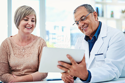Buy stock photo Shot of a doctor showing his patient something on his digital tablet