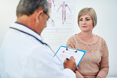 Buy stock photo Shot of a doctor filling in some information on a patient's medical chart