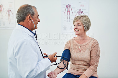 Buy stock photo Shot of a male doctor checking his patient's blood pressure