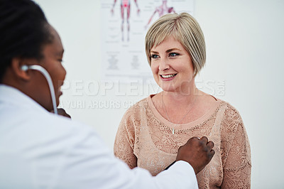Buy stock photo Shot of a female doctor checking her patient's heartbeat