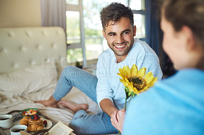 Buy stock photo Shot of a sweet man giving his girlfriend a flower