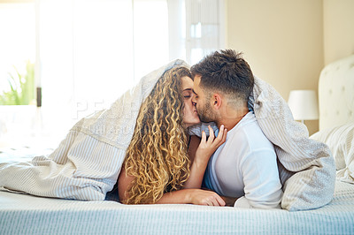 Buy stock photo Shot of an affectionate young couple spending time together in their bedroom
