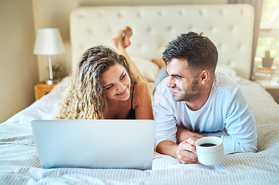 Buy stock photo Shot of a young couple using their laptop while relaxing in their bedroom