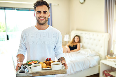 Buy stock photo Shot of a young man serving his girlfriend breakfast in bed