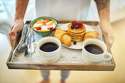 Buy stock photo Cropped shot of an unrecognizable young man carrying breakfast into the bedroom on a tray