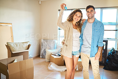 Buy stock photo Shot of a young couple packing boxes while moving house