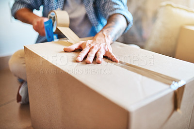 Buy stock photo Cropped shot of a young man sealing a box while moving house