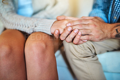 Buy stock photo Cropped shot of a young couple holding hands on the sofa at home
