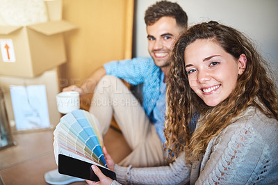 Buy stock photo Shot of a young couple looking at colour swatches while moving into their new home