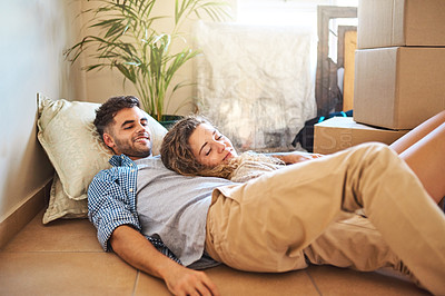 Buy stock photo Shot of a happy young couple relaxing on the floor of their new home