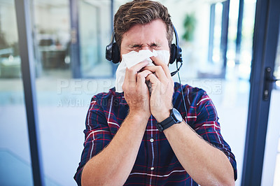 Buy stock photo Shot of a young man blowing his nose while working in a call centre