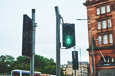Buy stock photo Shot of a pedestrian traffic light with city buildings situated in the background outside during the day