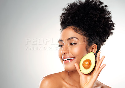 Buy stock photo Studio shot of a beautiful young woman looking thoughtful while holding an avocado against a gray background