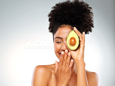 Buy stock photo Studio shot of a beautiful young woman holding an avocado while posing against a gray background