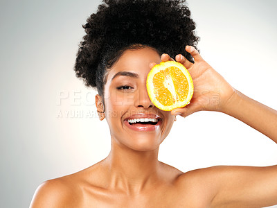 Buy stock photo Studio portrait of a beautiful young woman holding an orange while posing against a gray background