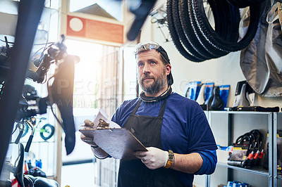 Buy stock photo Shot of a handsome man working in his self-owned bicycle workshop