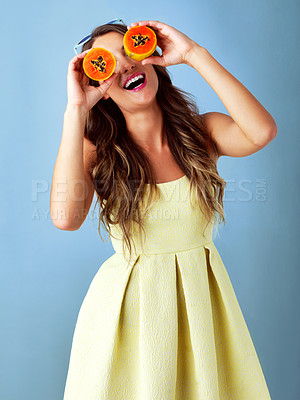 Buy stock photo Studio shot of a young woman covering her eyes with papaya slices against a blue background