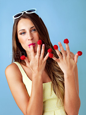 Buy stock photo Studio shot of a woman eating raspberries off her fingertips against a blue background