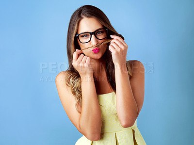 Buy stock photo Studio shot of a woman playfully making a moustache with her hair against a blue background