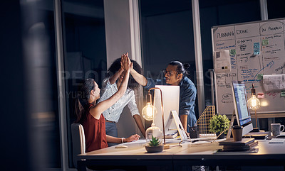 Buy stock photo Cropped shot of three young creative businesspeople high fiving during a meeting in their office at night