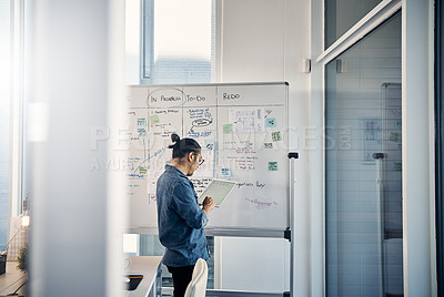 Buy stock photo Cropped shot of a handsome young creative businessman working on a whiteboard in his office