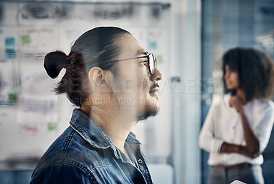 Buy stock photo Cropped shot of a handsome young creative businessman working in his office with a colleague in the background