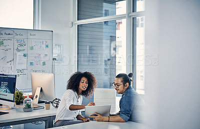 Buy stock photo Cropped shot of two young creative businesspeople working on a tablet in their office