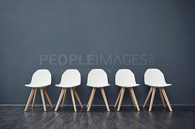 Buy stock photo Shot of a row of empty chairs against a grey background inside of a studio