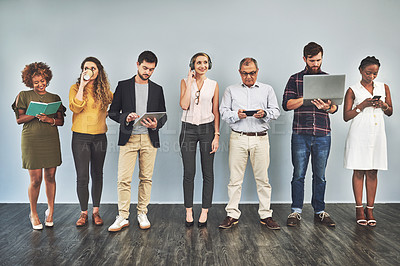 Buy stock photo Shot of a group of business people using their smart devices while standing against a wall