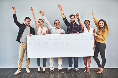 Buy stock photo Shot of a group of creatives holding up a placard